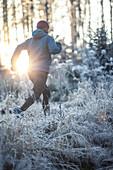 Junger Mann läuft durch einen mit Frost bedeckten Wald, Allgäu, Bayern, Deutschland