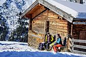 Frau und Mann auf Skitour sitzen an Almhütte und machen Pause, Tuxer Alpen, Tirol, Österreich