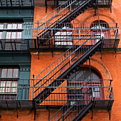 'Brick residential building with black metal fire escapes, Soho, Lower Manhattan; New York City, New York, United States of America'