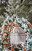 'Hoarfrost covers holiday decorations on antique bird cage and hops arbor, Christmas season; Minnesota, United States of America'