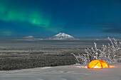 'Green Aurora Borealis shines above moonlight casting light on Mount Drum and the Copper River Valley, a glowing tent on a foggy winter night, Copper River Valley, South-central Alaska; Alaska, United States of America'