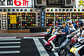 'The motorbikes and scooters in Taibei city are really a big number, helmet shop in view with scooters stopped on the road; Taiwan, China'