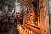 'Lit candles by a Virgin and Child icon in the interior of Gergeti Trinity Church; Kazbegi, Mtskheta-Mtianeti, Georgia'