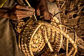'Local craftsman weaving a basket; Maputo, Mozambique'