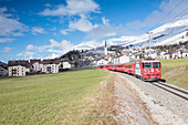 The red train runs across the alpine village of Zuoz in spring, Maloja, Canton of Graubunden, Engadine, Switzerland, Europe