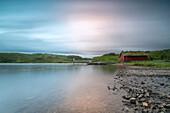 Pink lights of the midnight sun illuminate sea and the typical rorbu, Holdalsvatnet, Vestvagoy, Lofoten Islands, Norway, Scandinavia, Europe