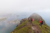 Hikers on top of rocky peak admire the blue sea surrounded by mist, Reinebringen, Moskenesoya, Lofoten Islands, Norway, Scandinavia, Europe