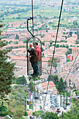 Europe, Italy, Umbria, Gubbio, two people in a cable car with Gubbio town in the background