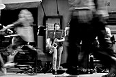 Bologna street photography, Musicians perform on the street in front of public on the move