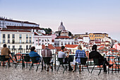 Tourists admire terracotta roofs and ancient dome from a terrace at Miradouro Alfama viewpoint of Lisbon Portugal Europe