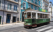 A typical tram takes tourists to discover the old city of Lisbon with its architecture and colorful houses Portugal Europe