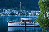New Zealand, South Island, Otago, Queenstown, harbor view with boat, dusk.