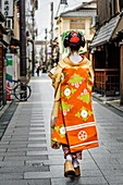Maiko dressed with traditional attires posing to the camera in a small alley on her way to work.