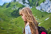 Sensitive female child with closed eyes and streaming hair enjoying the breeze of nature during hiking adventure in Bavarian mountains, Brauneck, Germany