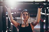 Close-up of young woman doing chin-ups at gym