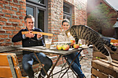 Playful man aiming toy rifle on tabby cat while sitting with woman in back yard