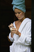 Young woman in bathrobe holding yoghurt in bowl at home