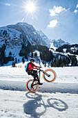 Ein junger Mann zeigt ein Wheelie auf einem Fatbike, Snowbike, Mountainbike vor dem zugefrorenen Lauenensee (Louwenesee) in der Nähe von Gstaad, Berner Oberland, Schweiz
