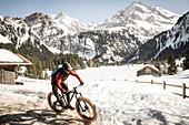 Ein junger Mann auf einem Fatbike, Snowbike, Mountainbike vor dem zugefrohrenen Lauenensee (Louwenesee) in der Nähe von Gstaad, Berner Oberland, Schweiz