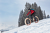 Ein junger Mann auf einem Fatbike, Snowbike, Mountainbike bei Sparenmoos oberhalb von Gstaad, Berner Oberland, Schweiz