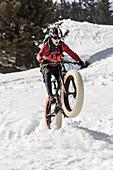Ein junger Mann auf einem Fatbike, Snowbike, Mountainbike bei Sparenmoos oberhalb von Gstaad, Berner Oberland, Schweiz.