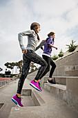 Caucasian women running on stadium staircase