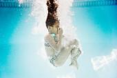 Hispanic girl swimming underwater holding nose