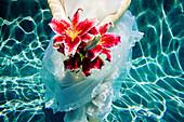 Caucasian woman wearing dress holding bouquet of flowers underwater