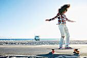 Hispanic woman riding skateboard at beach