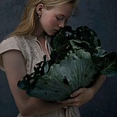 Caucasian girl smelling leafy green lettuce