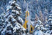 Trees with pristine snow and yellow church, St Moritz, Engadine, Switzerland