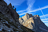 Hikers climb rocks to admire peaks Furcella De Furcia Odle Funes Valley South Tyrol Dolomites Trentino Alto Adige Italy Europe