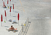 High angle view of women sunbathing at beach during sunny day