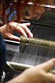 France, Calais, Pas-de-Calais (62), Lace factory. A worker filling a thread reel up.