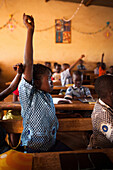 Burkina Faso, Ouagadougou, Girl raising her hand in class
