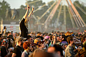 France, crowd at the Hellfest festival in Clisson. A woman photographed raising her arms on the shoulders of a man