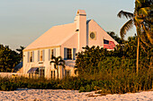 A noble residential building with an American flag and palm trees directly on the beach, Boca Grande, Florida, USA