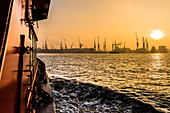 Sunrise in the Hamburg port with view at docks and cranes seen from the Elbe ferry, Hamburg, Germany