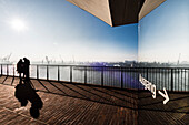 A couple in the morning atmosphere at the plaza Elbphilharmonie with view of the docks, Hamburg, Germany