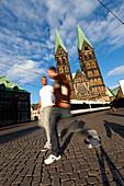 Men walking on Marktplatz by the St. Petti Dom, Bremen, Germany