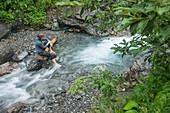 Junge Wanderin macht eine Pause an der Trettach auf dem Weg zur Kemtpener Hütte in den Alpen