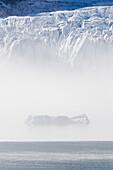 Small iceberg in the mist in front of glacier Seligerbreen, Liefdefjorden, Spitzbergen, Svalbard