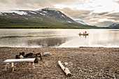 Two girls and a woman rowing a boat on Teusajaure. Kungsleden trekking. Laponia, Lapland, Sweden.