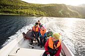 Zwei Mädchen, eine Frau und ein Mann in einem Motorboot. Bootstaxi mit dem Hüttenwart Roland Lindholm über den See Teusajaure. Kungsldeden Trekking. Laponia, Lappland, Schweden.