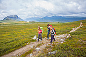 Two girls and one woman hike on the Kungsleden trekking, stage Saltoluokta to Sitojaurestugorna. Laponia, Lapland, Sweden.