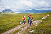 Zwei Mädchen und eine Frau wandern auf dem Kungsleden Trekking, Etappe Saltoluokta zur Sitojaurestugorna. Laponia, Lappland, Schweden.