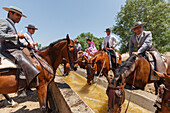 Horse riders at a water trough, El Rocio pilgrimage, Pentecost festivity, Huelva province, Sevilla province, Andalucia, Spain, Europe