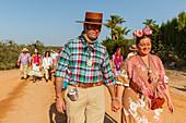 pilgrims, couple walking hand in hand, El Rocio pilgrimage, Pentecost festivity, Huelva province, Sevilla province, Andalucia, Spain, Europe