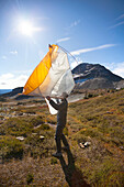 A Hiker Shakes Out His Tent Below Jim Kelly Peak In Illal Meadows