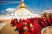 Buddhist monks praying around temple at Bouddha (Boudhanath), UNESCO World Heritage Site, Kathmandu, Nepal, Asia